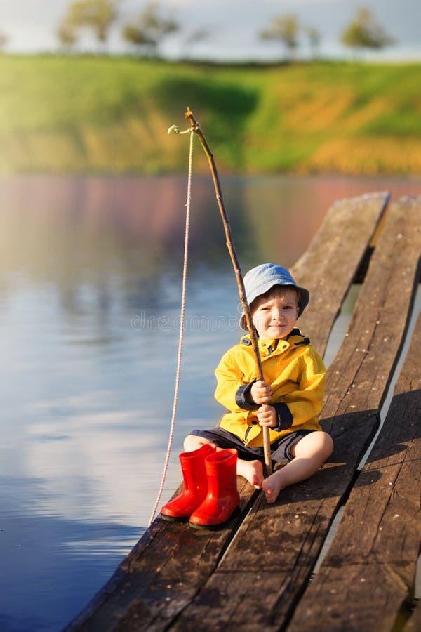 Αγόρι στην ξύλινη αποβάθρα με ένα δίχτυ του ψαρέματος στοκ φωτογραφίες