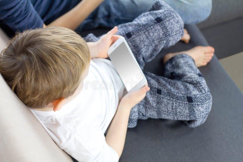 Αγόρι παιδιών που χρησιμοποιεί το κινητό τηλέφωνο Smartphone στα χέρια παιδιών Παιχνίδι μικρών παιδιών με το κινητό τηλέφωνο Έννο στοκ εικόνες