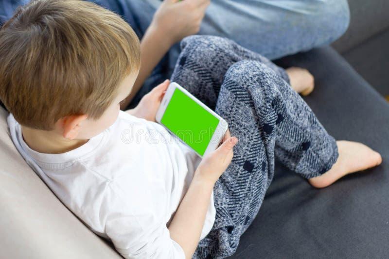 Αγόρι που κάθεται και που χρησιμοποιεί το κινητό έξυπνο τηλέφωνο με την πράσινη οθόνη στο σπίτι Κλείστε επάνω να τυλίξει αντίχειρ στοκ εικόνες με δικαίωμα ελεύθερης χρήσης