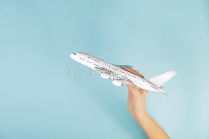Αεριωθούμενο πρότυπο αεροπλάνων στο ανθρώπινο χέρι στο μπλε υπόβαθρο στοκ εικόνες