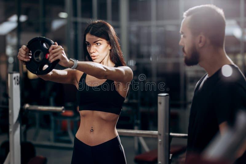 Αθλητικό κορίτσι που κάνει την άσκηση για τους μυς των όπλων με το βάρος στη γυμναστική κάτω από τη επίβλεψη ενός λεωφορείου στοκ φωτογραφίες με δικαίωμα ελεύθερης χρήσης