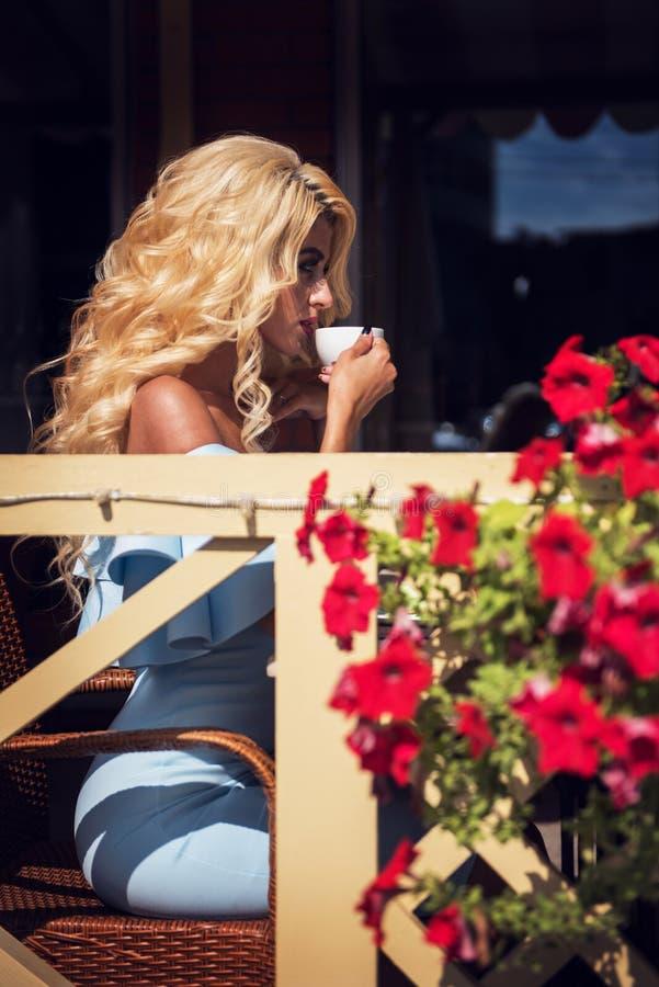 Αισθησιακή γυναίκα ομορφιάς στο κομψό μπλε φόρεμα στον καφέ στοκ φωτογραφία με δικαίωμα ελεύθερης χρήσης