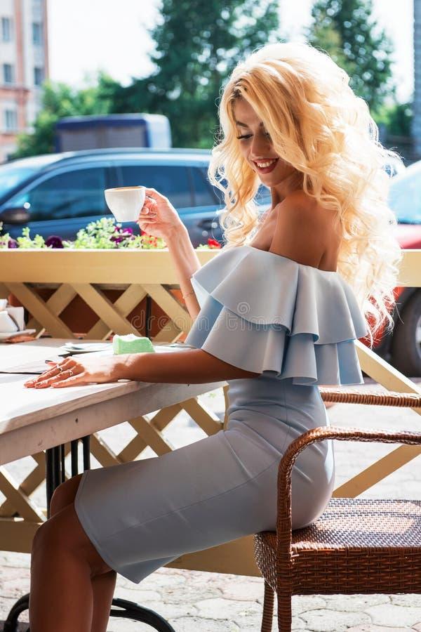 Αισθησιακή γυναίκα ομορφιάς στο κομψό μπλε φόρεμα στον καφέ στοκ φωτογραφίες