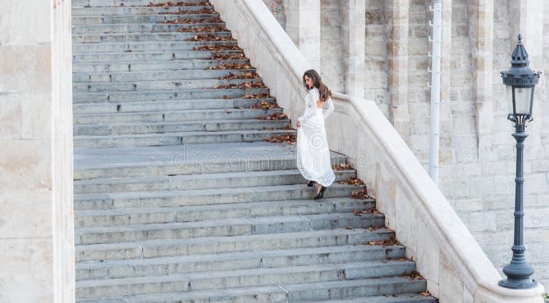 Αισθησιακή γυναίκα στη σκάλα Νύφη γυναικών στο άσπρο γαμήλιο φόρεμα, μόδα Το κορίτσι με τη γοητεία κοιτάζει Πρότυπο μόδας με πολύ στοκ φωτογραφία