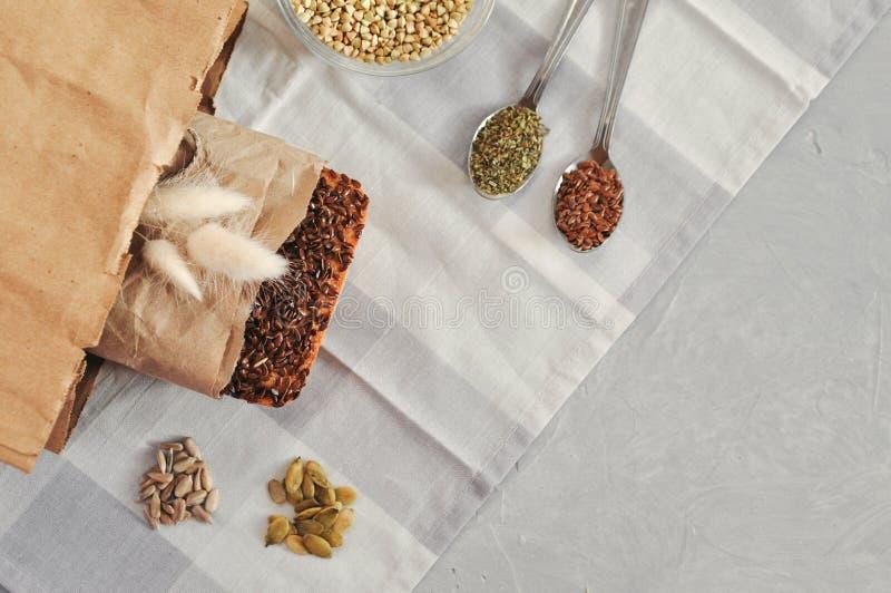 Ακατέργαστο σπιτικό vegan ψωμί μαγιάς φιαγμένο από πράσινο φαγόπυρο με τους σπόρους λιναριού, ηλίανθος, κολοκύθα σε μια τσάντα τη στοκ φωτογραφίες