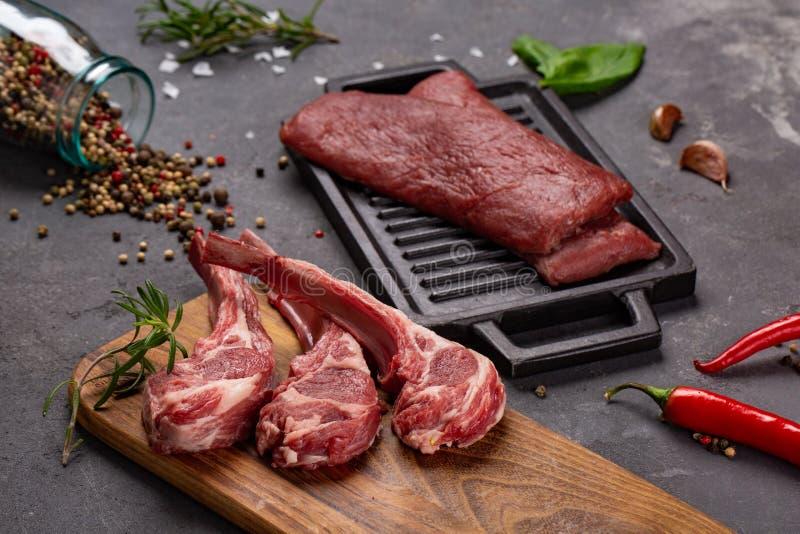 Ακατέργαστο φρέσκο πρόβειο κρέας κρέατος στα καρυκεύματα Chesno και Rosemary κόκκαλων σε ένα μαύρο υπόβαθρο στοκ φωτογραφίες με δικαίωμα ελεύθερης χρήσης