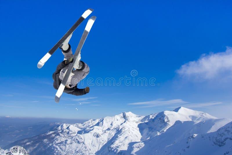 Ακραίος πηδώντας σκιέρ στο άλμα επάνω από τα βουνά στοκ φωτογραφία