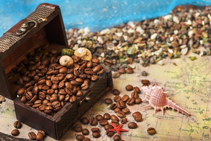 Ακόμα-ζωή Παλαιό ξύλινο στήθος και μαύρα χρυσά φασόλια καφέ Θαλασσινό κοχύλι και χάρτης ναυσιπλοΐας στοκ φωτογραφίες