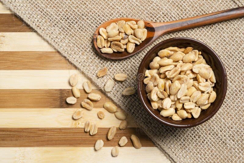 Αλατισμένα φυστίκια μέσα στην καφετιά αγγειοπλαστική και το ξύλινο κουτάλι στο ξύλινο υπόβαθρο μπαμπού στοκ φωτογραφίες