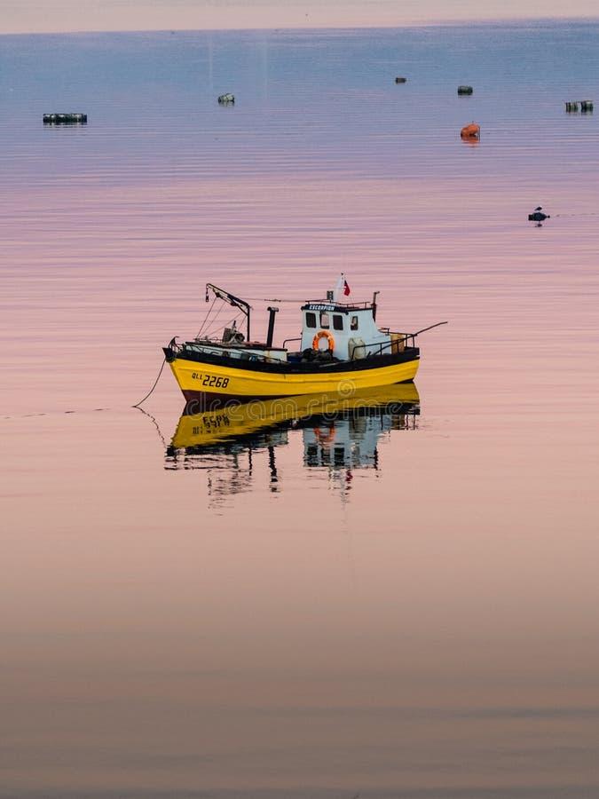 Αλιεία λίγης βάρκας που επιπλέει στο ήρεμο νερό κάτω από το καταπληκτικό ηλιοβασίλεμα σε Quellon, νησί Chiloe στη Χιλή στοκ εικόνες
