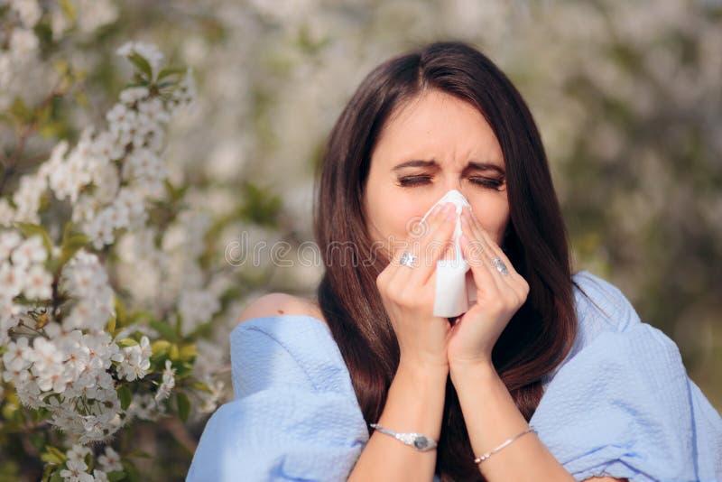 Αλλεργική γυναίκα που φυσά τη μύτη της δίπλα στο ανθίζοντας δέντρο στοκ φωτογραφία με δικαίωμα ελεύθερης χρήσης