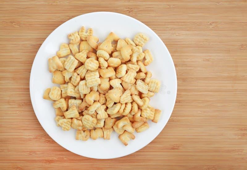 Αλφάβητο επιστολών κροτίδων ή μπισκότων ABC στο άσπρο πιάτο στο ξύλινο υπόβαθρο στοκ εικόνες