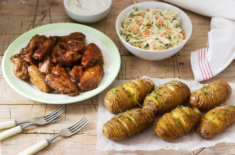 Αμερικανικά φτερά κοτόπουλου, hasselback πατάτες με τη σάλτσα και coleslaw σε ένα ξύλινο υπόβαθρο Αγροτικό ύφος στοκ εικόνα