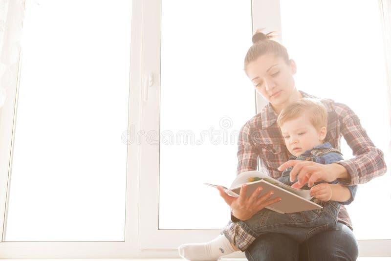 Ανάγνωση μητέρων με το γιο της σε ένα υπόβαθρο του παραθύρου στοκ εικόνα με δικαίωμα ελεύθερης χρήσης