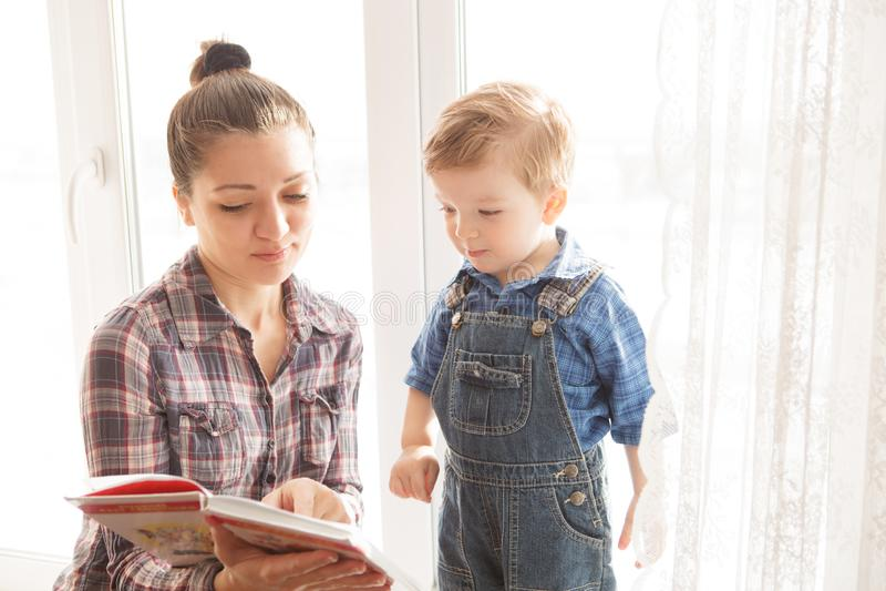 Ανάγνωση μητέρων με το γιο της σε ένα υπόβαθρο του παραθύρου στοκ φωτογραφία με δικαίωμα ελεύθερης χρήσης