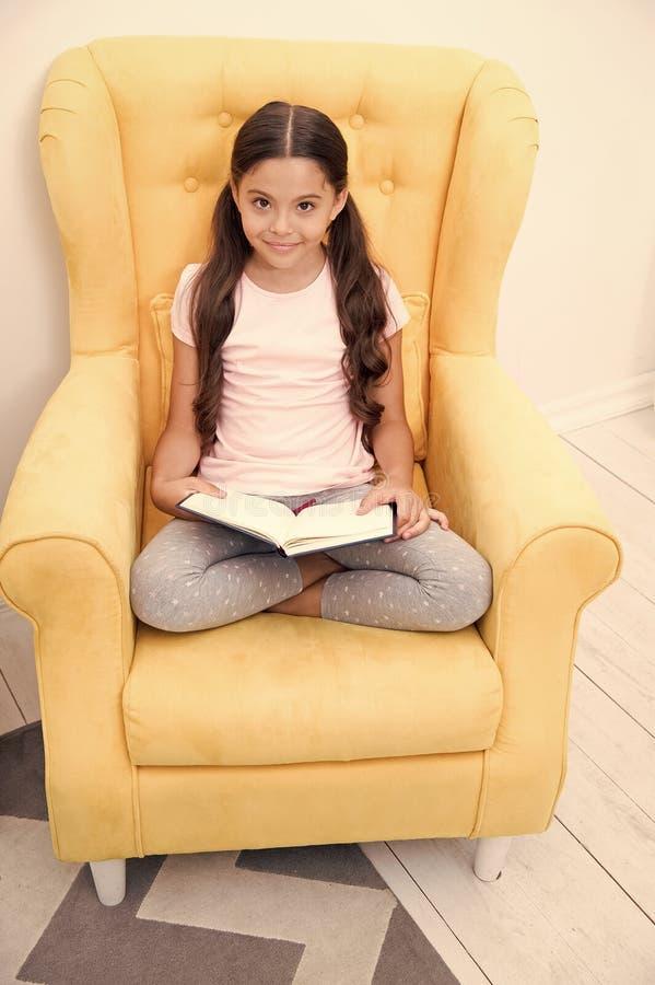 Ανάγνωση του χρήσιμου χόμπι Το παιδί κοριτσιών κάθεται το κίτρινο διαβασμένο πολυθρόνα βιβλίο Χαριτωμένη βιβλιόψειρα παιδιών Ευχά στοκ φωτογραφία
