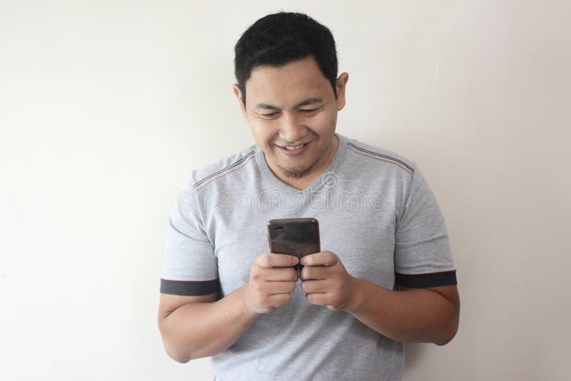 Ανάγνωση Texting νεαρών άνδρων που κουβεντιάζει στο τηλέφωνό του, χαμόγελο ευτυχές στοκ εικόνα με δικαίωμα ελεύθερης χρήσης