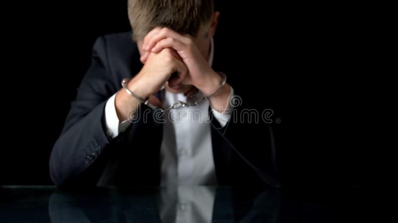 Ανήσυχο επιχειρησιακό άτομο στις χειροπέδες που κάθεται στο χώρο εργασίας, παράνομο εμπόριο, μαφία στοκ εικόνα με δικαίωμα ελεύθερης χρήσης