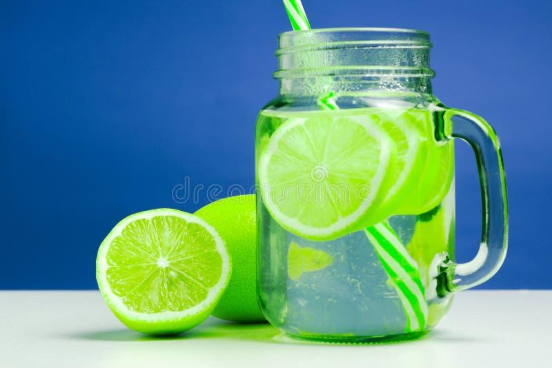 Αναζωογόνηση της πράσινης λεμονάδας εσπεριδοειδών στο βάζο θερινό κοκτέιλ με τα ώριμα και juicy λεμόνια και σε έναν άσπρο πίνακα στοκ εικόνα