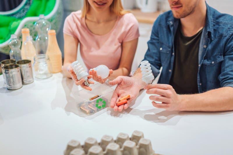 Ανακύκλωση, επαναχρησιμοποίηση Καλλιεργημένη άποψη των νέων μπαταριών εκμετάλλευσης ζευγών, λάμπες φωτός στα χέρια στοκ φωτογραφία