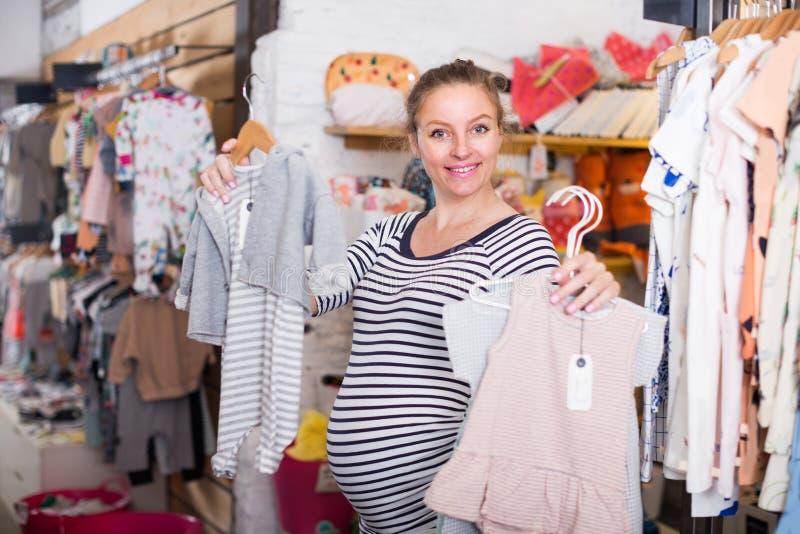 Αναμένουσα μητέρα στο ριγωτό φόρεμα αγορών τινίκ μέσα για τα μωρά στοκ φωτογραφία με δικαίωμα ελεύθερης χρήσης