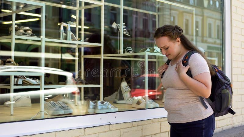 Ανατρέψτε το υπέρβαρο θηλυκό που φωνάζει μπροστά από τον ακριβό φτωχό σπουδαστή μπουτίκ παπουτσιών στοκ εικόνα