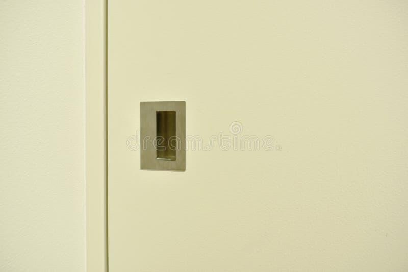 Ανοξείδωτη λαβή της άσπρης συρόμενης πόρτας στο εσωτερικό στοκ εικόνα