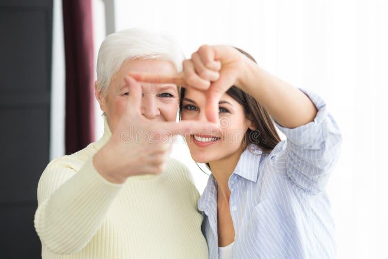 Ανώτερες γυναίκα και κόρη που πλαισιώνουν τα πρόσωπά τους στοκ φωτογραφίες