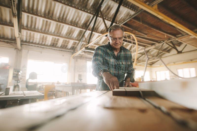 Ανώτερος ξυλουργός που κατασκευάζει τα ξύλινα προϊόντα στοκ φωτογραφίες