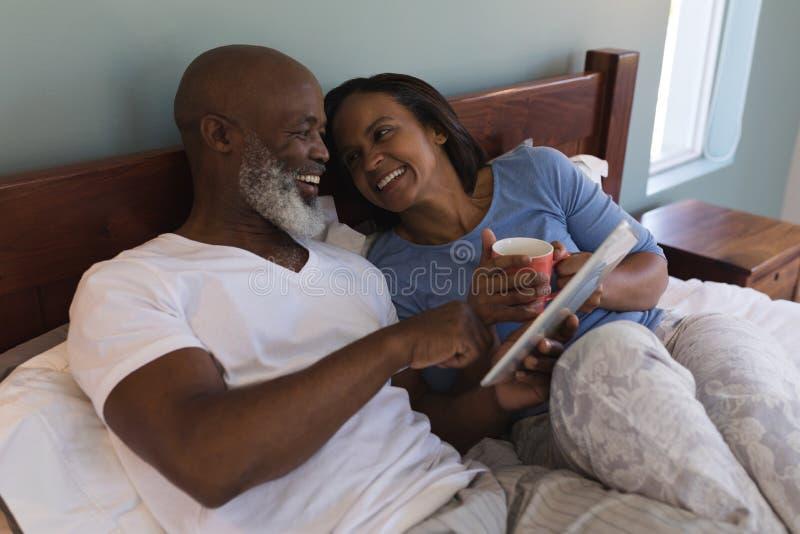 Ανώτερο ζεύγος χρησιμοποιώντας την ψηφιακή ταμπλέτα και πίνοντας τον καφέ στην κρεβατοκάμαρα στοκ εικόνα
