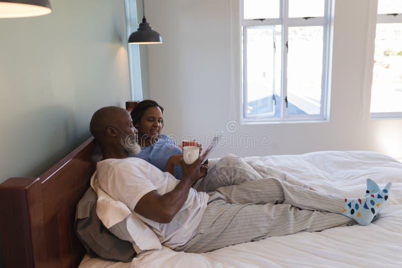 Ανώτερο ζεύγος που χρησιμοποιεί την ψηφιακή ταμπλέτα απολαμβάνοντας ένα φλιτζάνι του καφέ στην κρεβατοκάμαρα στοκ εικόνες