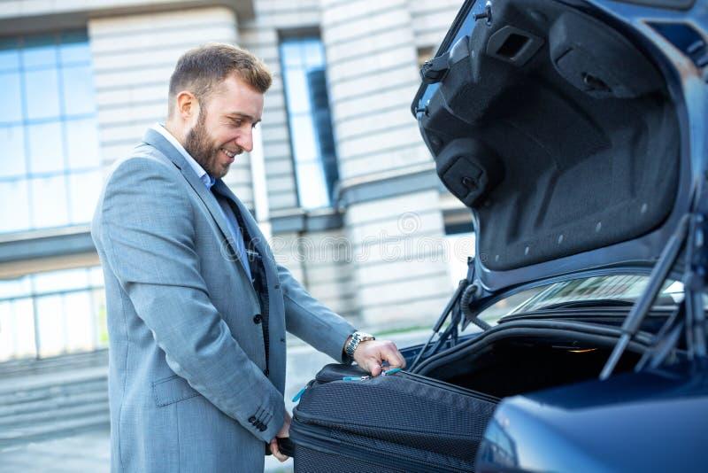 Αριστοκρατικό άτομο που τοποθετεί τις αποσκευές στον κορμό του αυτοκινήτου στοκ φωτογραφία με δικαίωμα ελεύθερης χρήσης