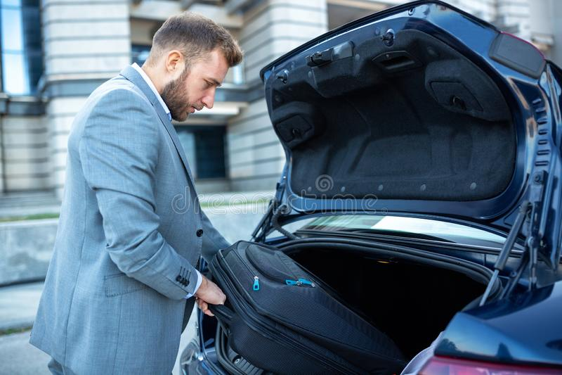 Αριστοκρατικό άτομο που τοποθετεί τις αποσκευές στον κορμό του αυτοκινήτου στοκ εικόνες με δικαίωμα ελεύθερης χρήσης