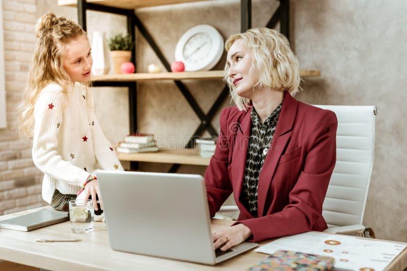 Αρκετά μακρυμάλλες μικρό κορίτσι που μιλά στην εργαζόμενη μητέρα της στοκ εικόνες