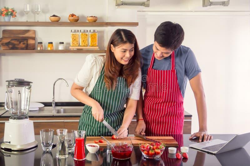 Αρκετά νέα κυρία που εξετάζει συνταγές καταφερτζήδων το lap-top TIF στοκ εικόνα