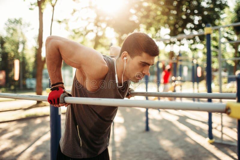 Αρσενικές ασκήσεις αθλητών στους παράλληλους φραγμούς υπαίθριους στοκ εικόνα