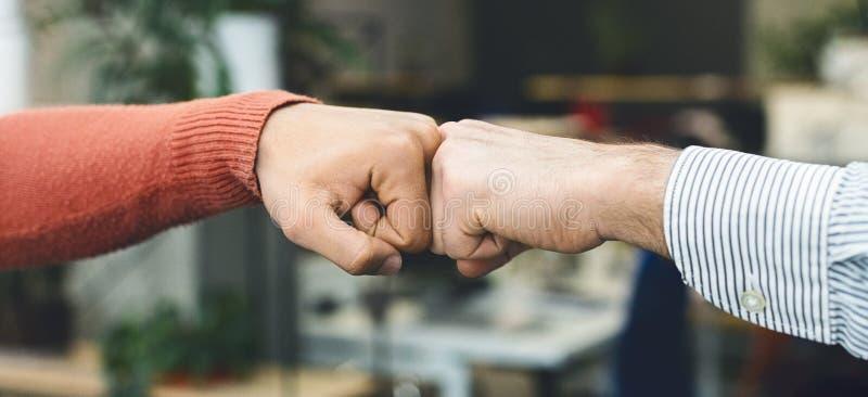 Αρσενικοί φίλοι που χαιρετούν ο ένας τον άλλον με την πρόσκρουση πυγμών στοκ εικόνες