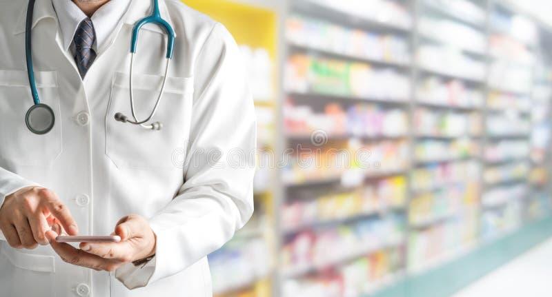 Αρσενικός φαρμακοποιός που χρησιμοποιεί το κινητό τηλέφωνο στο φαρμακείο στοκ εικόνες με δικαίωμα ελεύθερης χρήσης