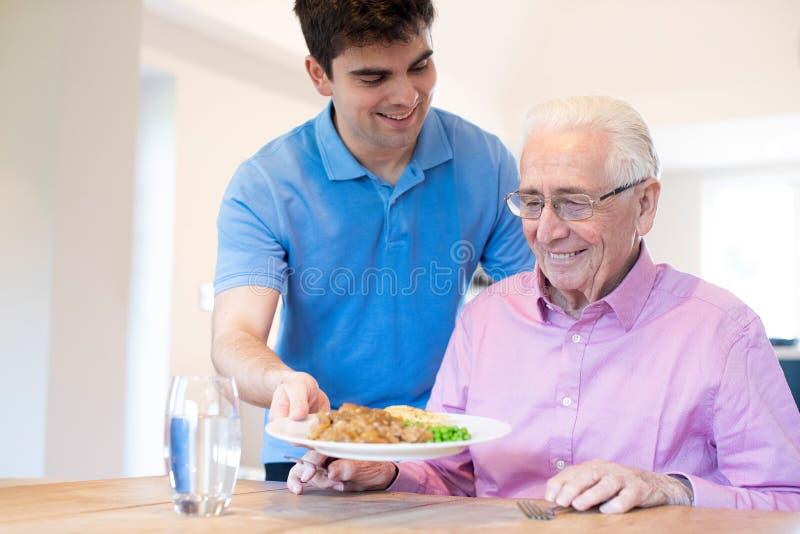 Αρσενικό βοηθητικό εξυπηρετώντας γεύμα προσοχής στο ανώτερο αρσενικό που κάθεται στον πίνακα στοκ φωτογραφία
