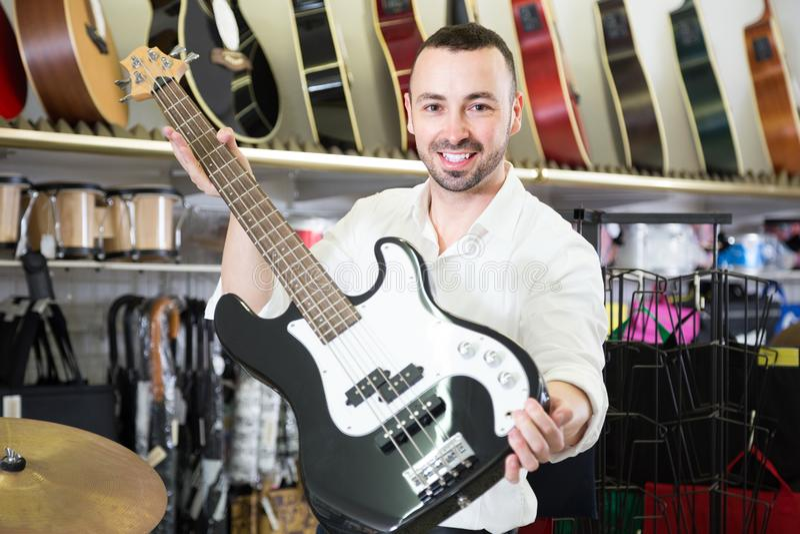 Αρσενικό που αγοράζει τη νέα κιθάρα στοκ εικόνες