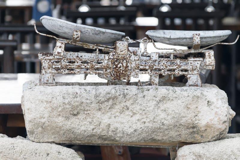 Αρχαίες εκλεκτής ποιότητας σκουριασμένες κλίμακες ή ζυγίζω-μηχανή φιαγμένες από μέταλλο και πέτρες σε ένα θολωμένο υπόβαθρο υπαίθ στοκ εικόνα