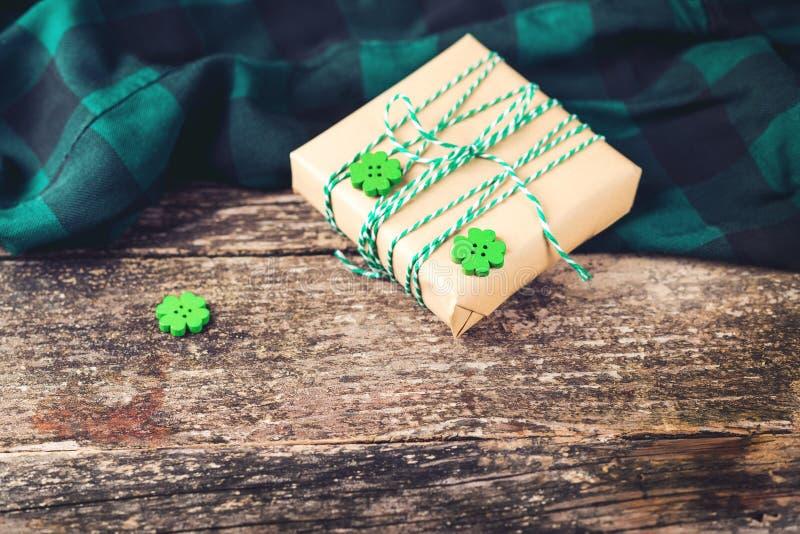 Αρχικό κιβώτιο δώρων στον παλαιό ξύλινο πίνακα Έννοια πώλησης διακοπών Το παρόν και πράσινο τριφύλλι τριφυλλιών βγάζει φύλλα στοκ φωτογραφίες με δικαίωμα ελεύθερης χρήσης