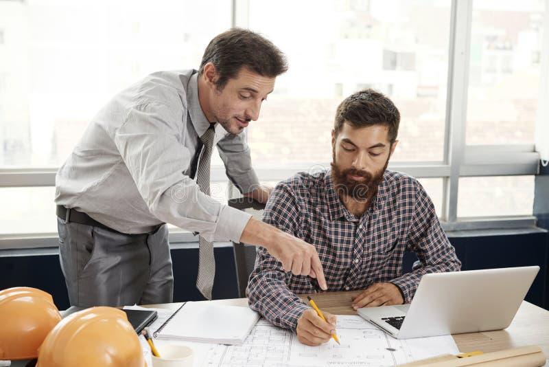 Αρχιτέκτονας που βοηθά το συνάδελφο στοκ φωτογραφία με δικαίωμα ελεύθερης χρήσης