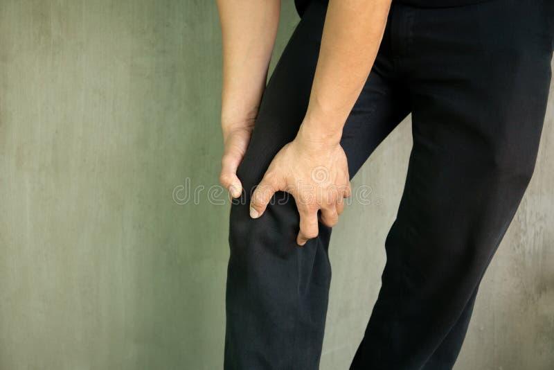 Αρπαγή ατόμων το γόνατό του που δοκιμάζει τον πόνο που απομονώνεται στο γκρίζο υπόβαθρο στοκ φωτογραφίες με δικαίωμα ελεύθερης χρήσης