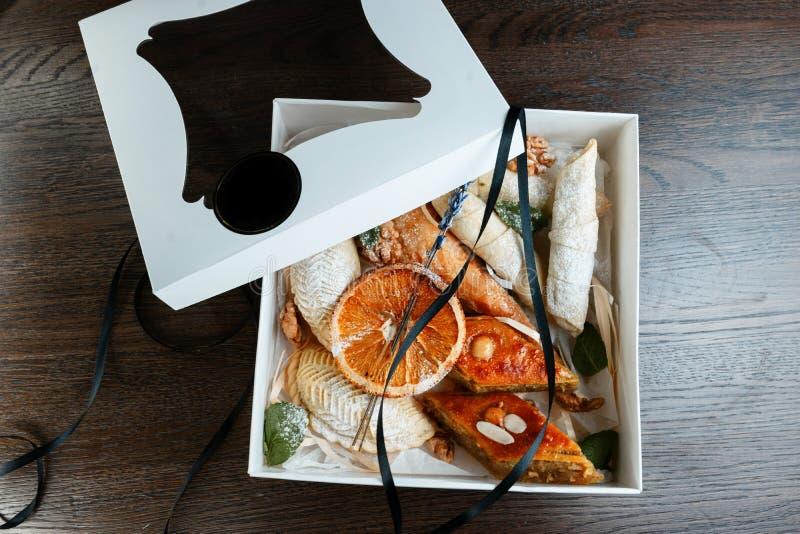 Ασιατικά γλυκά σε ένα εκλεκτής ποιότητας κιβώτιο δώρων που διακοσμείται με lavender, τη μαύρη κομψή κορδέλλα, τις ξηρά πορτοκαλιά στοκ φωτογραφίες