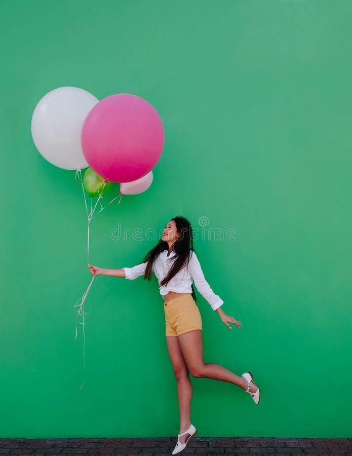 Ασιατική γυναίκα με μια δέσμη των ζωηρόχρωμων μπαλονιών στοκ εικόνες