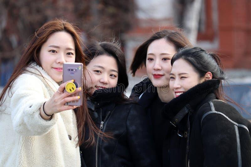 Ασιατικοί τουρίστες κοριτσιών που παίρνουν selfie με ένα smartphone στο κόκκινο τετράγωνο στη Μόσχα στοκ φωτογραφία με δικαίωμα ελεύθερης χρήσης