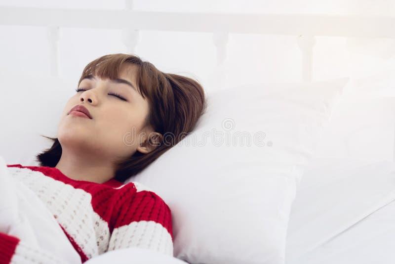Ασιατικός ύπνος γυναικών στο άσπρο μαξιλάρι στο κρεβάτι στην κρεβατοκάμαρα στις διακοπές ευτυχής χαλαρώστε το χρόνο στοκ φωτογραφία