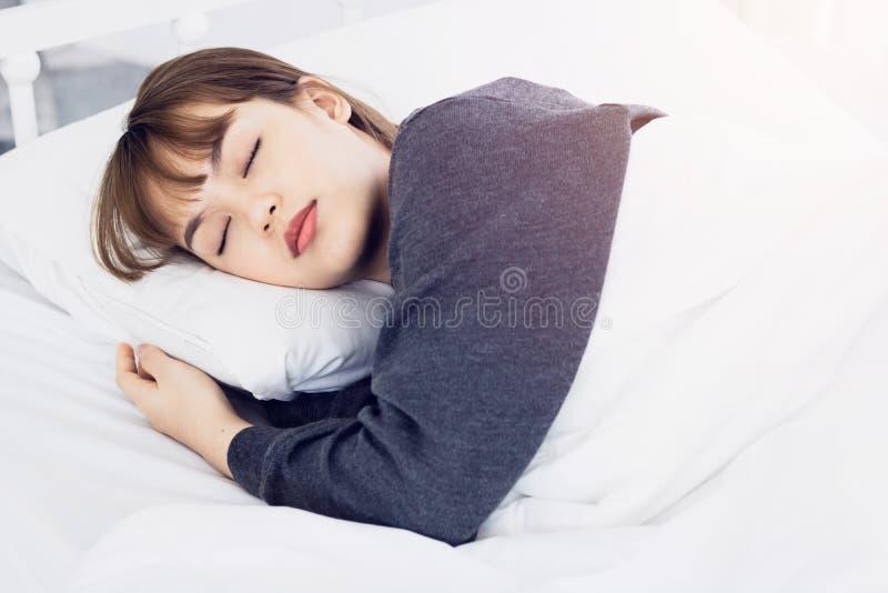 Ασιατικός ύπνος γυναικών στο άσπρο μαξιλάρι στο κρεβάτι στην κρεβατοκάμαρα στις διακοπές ευτυχής χαλαρώστε το χρόνο στοκ φωτογραφία με δικαίωμα ελεύθερης χρήσης