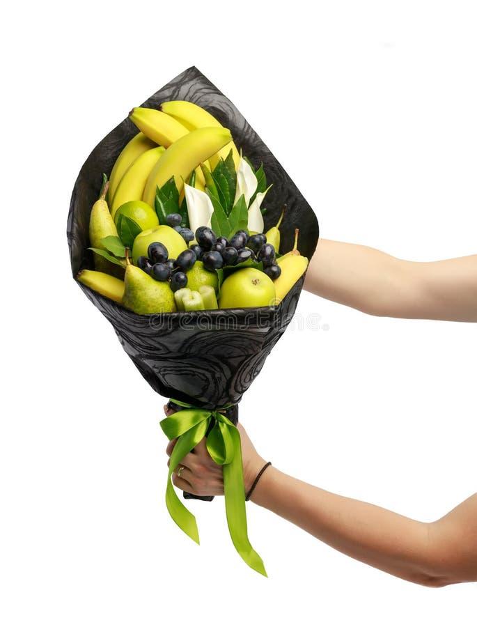 Ασυνήθιστη εδώδιμη ανθοδέσμη που αποτελείται από τις μπανάνες, τα αχλάδια, τα μήλα, τον ασβέστη και τα μαύρα σταφύλια στα χέρια μ στοκ φωτογραφία με δικαίωμα ελεύθερης χρήσης